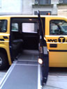 photo of a ramp extended outside of a yellow Nissan MV-1