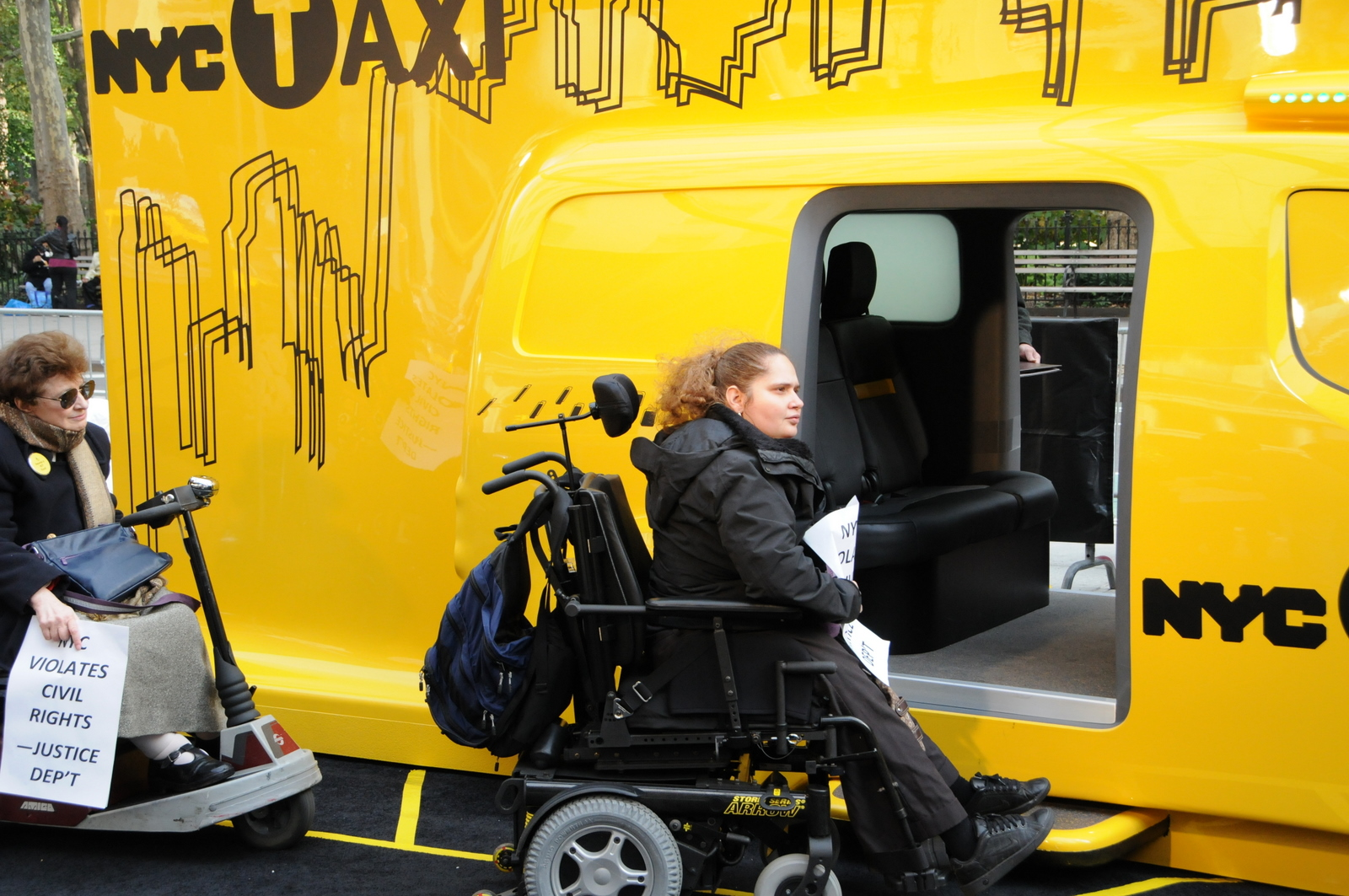 larger photo of a woman in a wheelchair at an inaccessible entrance to the taxicab