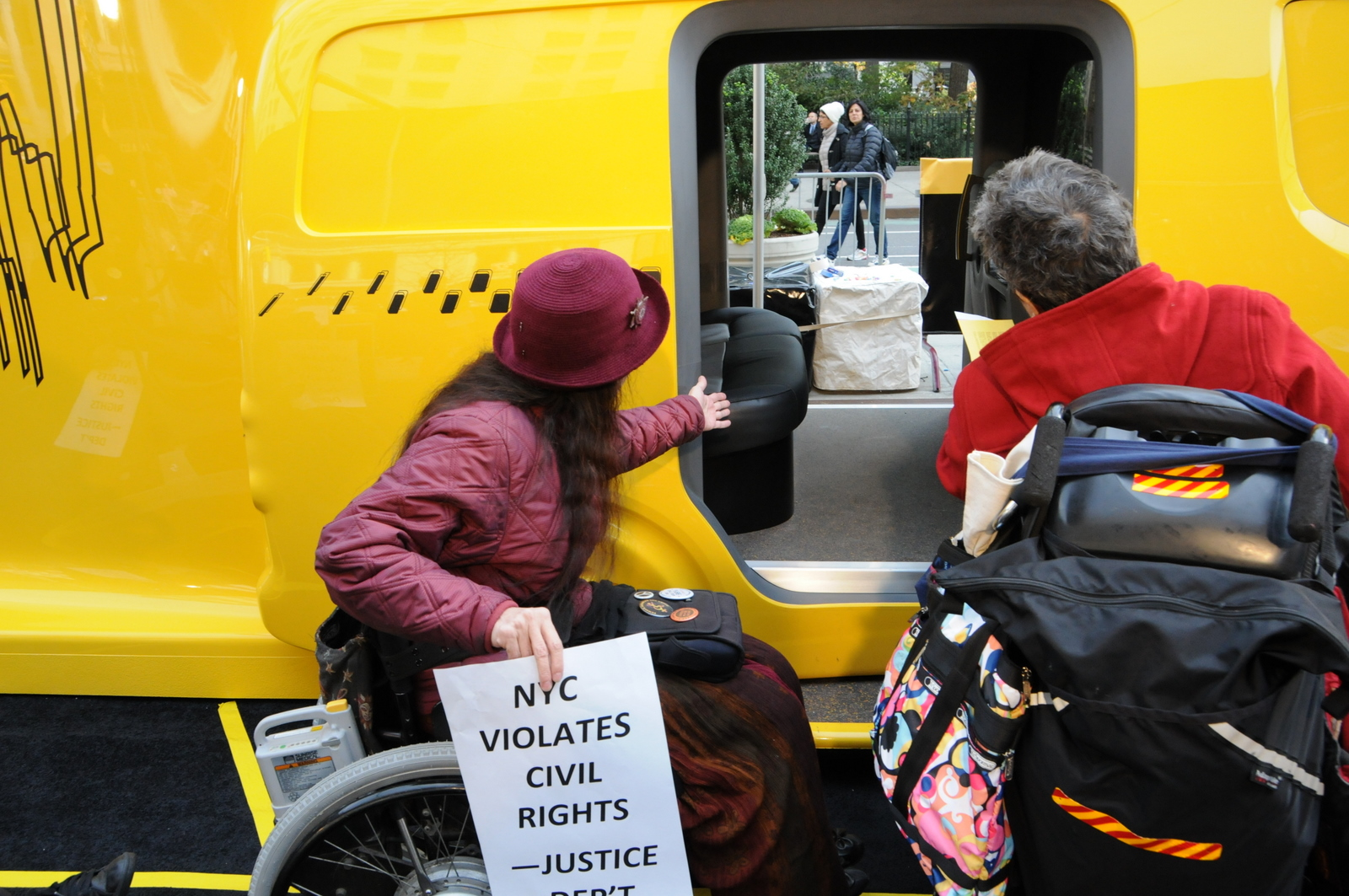 photo of women in wheelchairs in front of inaccessible entrance to Taxi of Tomorrow