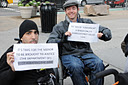 photo of two wheelchair users holding signs