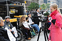 photo of a news camera filming, or ready to film, protestors in wheelchairs