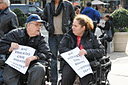 photo of two of the demonstrators, in wheelchairs, chatting with each other