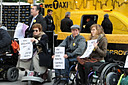 photo of some demonstrators, mostly in wheelchairs, in front of Taxi of Tomorrow